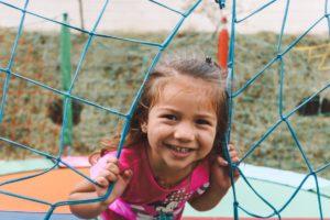 Little girl looking through goal nets